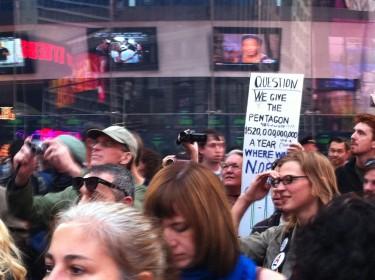 Manifestantes pasando por el índice de Nasdaq en Times Square. Foto de Robert Valencia para Global Voices, 2011