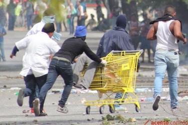 El estudiante asesinado, Willy Florian, siendo llevado por encapuchados fuera de la zona de disturbios.