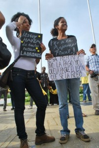 Young people hold up signs outside the National Congress, in protest against the Fiscal Reform.