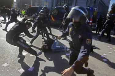 Madrid: polícia anti-motim rodeia um jovem caído no chão. Fotografia da página de Facebook «AntenapezTV»