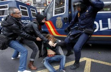 Madrid: um agente pontapeia uma jovem enquanto dois manifestantes tentam salvá-la. Fotografia da página de Facebook «AntenapezTV»