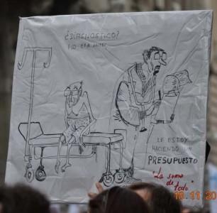 Cartel en una manifestación: «¿Diagnóstico? Eso era antes. Le estoy haciendo un presupuesto». Foto de la página de Facebook «A disfrutar de lo votado»