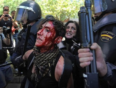 Riot police detain a young woman injured at a protest. Photo from the blog «El aullido» [The Howl]