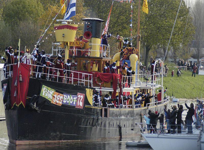 San Nicolás, rodeado de sus ayudantes Zwarte Piet, saluda desde el barco que lo trae de España. Foto de 12Danny12 en Wikimedia Commons con licencia copyleft.