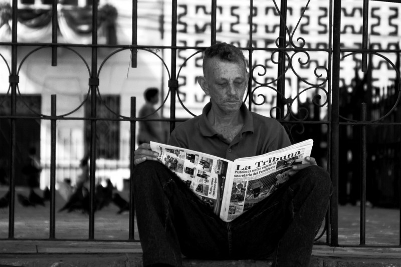 "Man reading a newspaper with the headline ""Gunmen kill husband of President's secretary"". Photo by Gabriel Vallecillo on Flickr, under a Creative Commons license  (CC BY-NC-ND 2.0)"