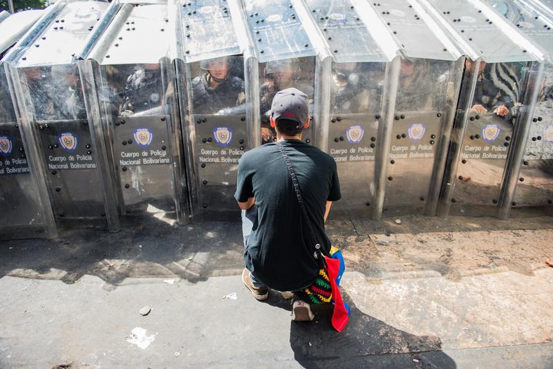Joven tratando de persuadir a la policía en Caracas el 12 de febrero. Foto de Carlos Becerra, copyright Demotix.