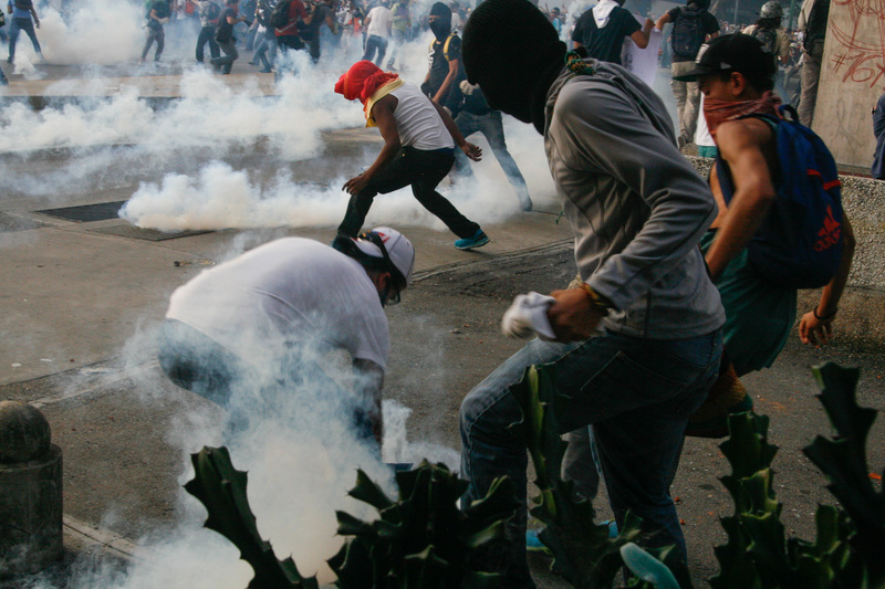 Manifestantes esquivan gases lacrimógenos lanzados por la Guardia Nacional. 19 de febrero, 2014. Altamira, Caracas. Foto de Sergio Alvarez, copyright Demotix.