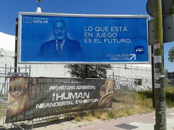 Valla publicitaria del PP junto al anuncio de una exposición de hombres de neandertal. Foto subida a Twitter por Patricia F de Lis