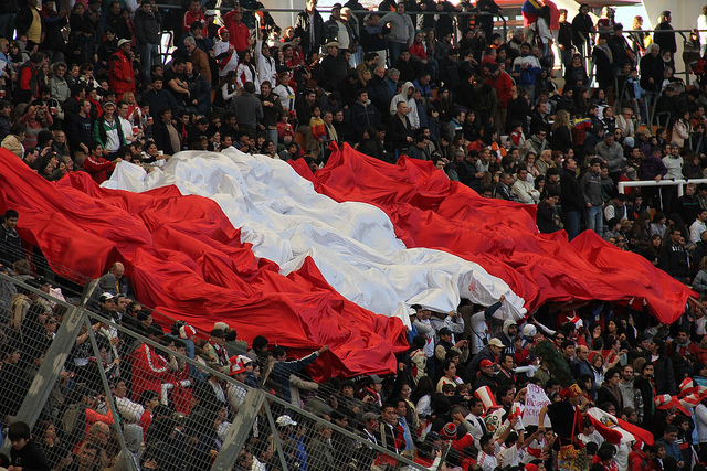 "The Peruvian flag in the crowd during a football match. Image on Flickr by user <a href=""https://www.flickr.com/photos/teruhn/8490288381"">Teru Kaleru</a>. CC BY-NC-ND 2.0."