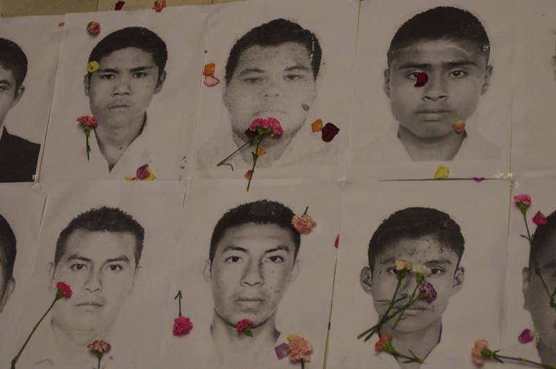 Fotos de los estudiantes mexicanos desparecidos con claveles durante Acto simbolico frente a la embajada de Mexico en Bogota, Colombia el viernes 7 de Noviembre 2014. Foto de Flickr de la Agencia Prensa Rural.