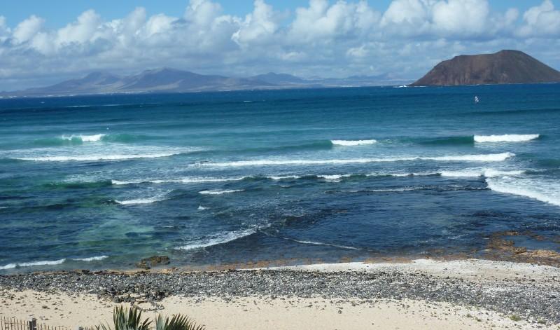 Playa de Corralejo, en Fuerteventura, con la silueta de Lanzarote al fondo, cerca de la zona de prospecciones. Foto de la autora.