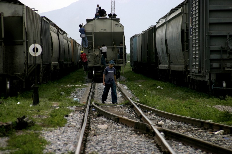 "Central American migrants hop a freight train in Ciudad Ixtepec, Mexico on July 15, 2008. The trains are nicknamed ""La Bestia"" - the Beast - and will take them on a perilous journey 1,500 miles north to the U.S.-Mexican border. Canada's SAWP program flies workers in on a plane. Photo by Peter Haden."