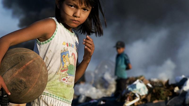 Una niña en el vertedero de basura de La Chureca Landfill busca juguetes y otros objetos de interés. Los trabajadores de vertederos llevan una vida difícil en el basurero a cielo abierto más grande de América Central. Fotografía tomada por Misha Tulek. Copyright © Demotix. 13/10/2009
