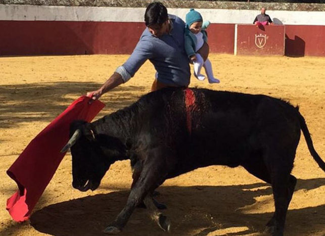 Спорное фото Франа Риверы, который бьется с быком и одновременно держит на руках свою дочь. Опубликовано eldiario.es по лицензии CC BY-SA 3.0.