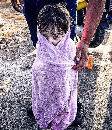 Una niña intenta entrar en calor a su llegada a las costas griegas tras un peligroso viaje en una patera sobrecargada, 15 de agosto de 2015. Foto de Freedom House en Flickr, de dominio público