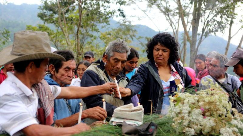 Berta Cáceres en Río Blanco, la región del oeste de Honduras en la que junto con el COPINH (Consejo Cívico de Organizaciones Populares e Indígenas de Honduras) se llevó a cabo la lucha por la defensa de la comunidad lenca contra los proyectos hidroheléctrica que amenazaban a la comunidad. Berta pasó años liderando la lucha hasta su asesinato a principios de marzo de este año. En la fotografía, Berta se reúne con otros miembros del COPINH para recordar a los miembros de la comunidad que fueron asesinados durante las luchas contra el Estado hondureño y las multinacionales. Fotografía de la Fundación Goldman. Publicada con permiso.