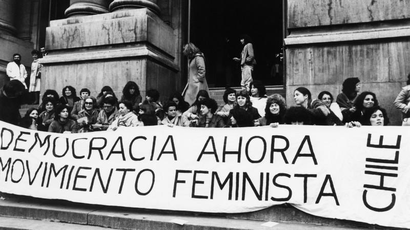 """""""Mujeres feministas se manifiestan en Santiago de Chile, pidiendo democracia durante el gobierno militar de Augusto Pinochet."""" (de Kena Lorenzini) CC BY-SA 3.0"""