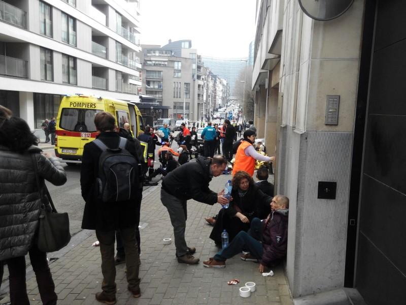 Varios heridos en el atentado de la estación de Maalbeek reciben asistencia de los transeúntes mientras esperan a los servicios de urgencias. Foto de la autora.