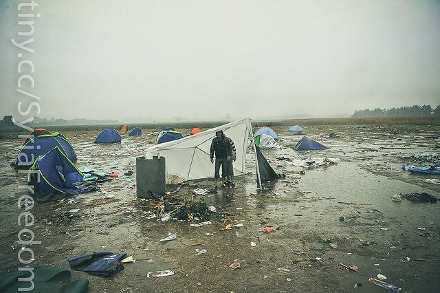 Emigrantes y refugiados intentan protegerse de la lluvia mientras esperan para cruzar la frontera entre Grecia y Macedonia en Idomeni, 10 de Septiembre de 2015. Foto de Freedom House en Flickr, de dominio público