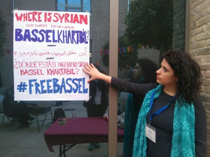 Leila señala un cartel que pide la libertad del desarrollador de software sirio, Bassel Khartabil. Foto cortesía de Leila.