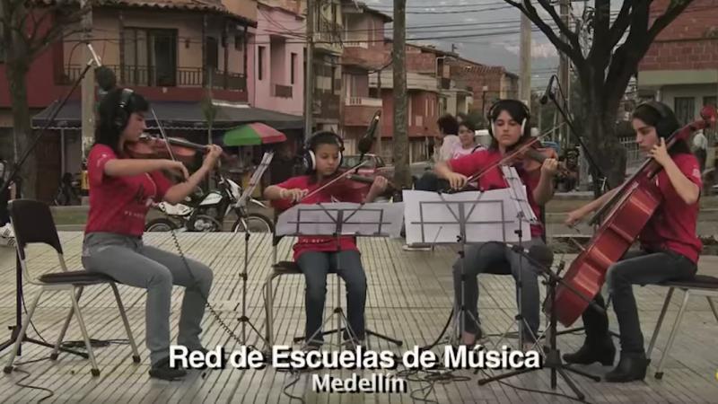 """Cuatro miembros de la Red de Escuelas de Música de Medellín tocan parte de """"La Tierra del Olvido"""" desde una de las comunas de Medellín. Captura de pantalla del video disponible en la cuenta de YouTube de Playing for a Change."""