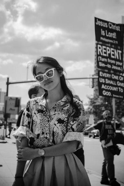 Photographie prise durant le festival de jazz de Détroit. Derrière cette jeune femme, qui fixe l'objectif sans la moindre timidité, se trouve un manifestant religieux parlant de pardon et de repentir. C'est un contraste frappant avec la jeune femme qui s'est arrêtée devant mon appareil photographique et s'est mise à poser sans que j'aie besoin de lui demander (Photographie prise par l'auteur, publiée avec son autorisation).