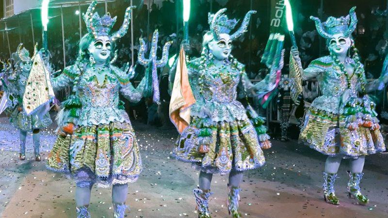 Des femmes en costume et portant des masques représentant des démons dansent dans la parade du carnaval