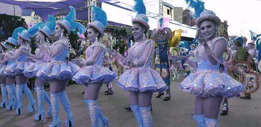 Des femmes incarnent le personnage de la Figure, en costume scintillant à jupe courte avec des bottes à talons hauts