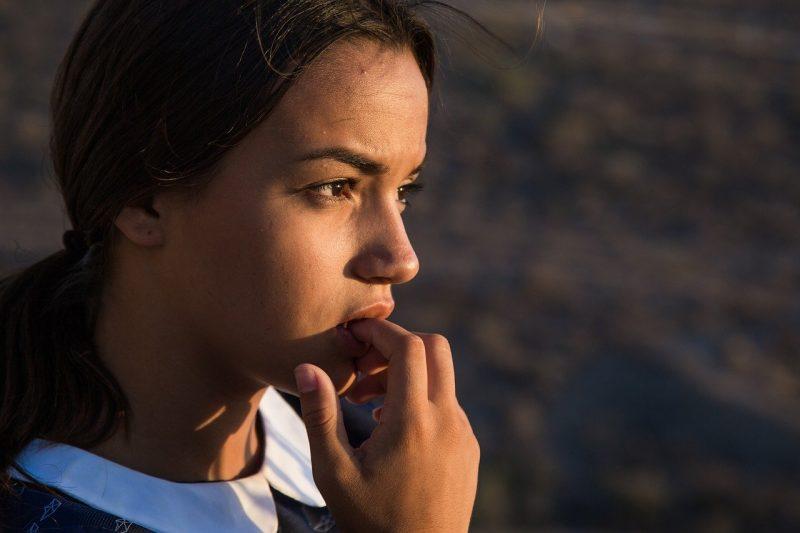Une jeune femme se mord les doigts, pensive