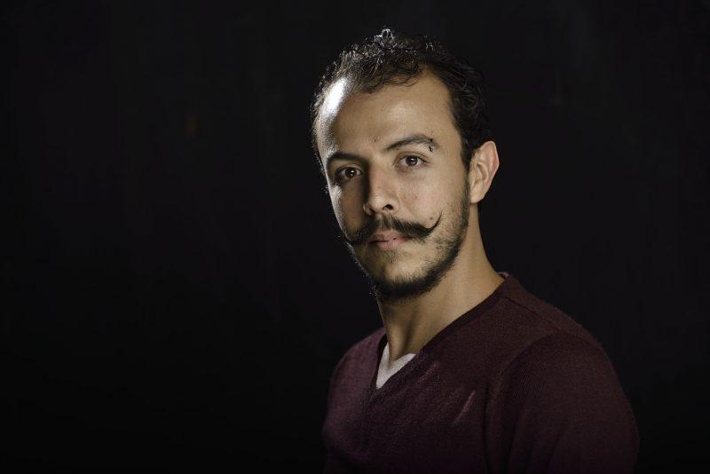 Portrait du comédien Juan Pablo Mazorra, sur fond noir. Son expression est neutre. Il porte une longue moustache.