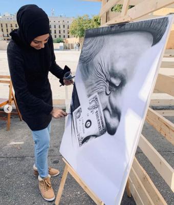 Batool entrain de peindre  en extérieur. La toile représente un vieil homme de profil et un billet de livre libanaise.