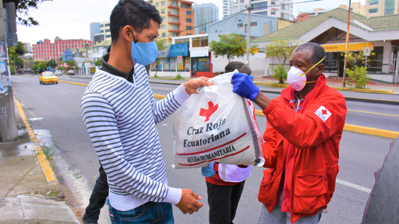 Un volontaire en veste rouge, portant des gants et un masque de protection faciale, transmet un sac de vivres à un habitant.
