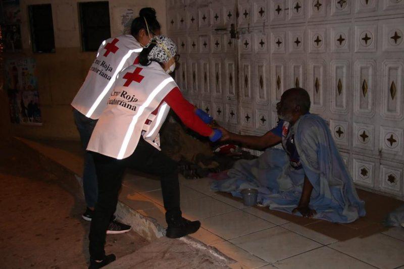 Deux femmes portant des gilets réfléchissants à l'effigie de la Croix-Rouge interviennent auprès d'un homme qui vit dans la rue.
