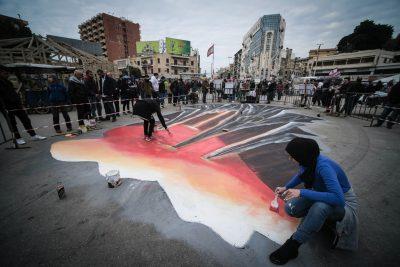 Batool Jacob réalise une peinture sur le sol avec son groupe. Derrière, on aperçoit les hauts immeubles de Tripoli.