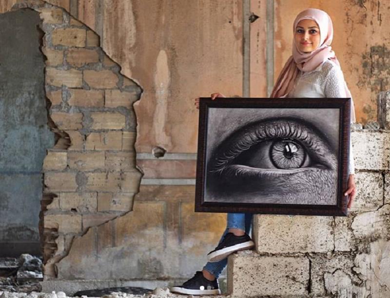 Batool Jacob, assise sur des marches en ciment apparent, tient un grand cadre photo où l'on voit un oeil en gros plan et en noir et blanc.