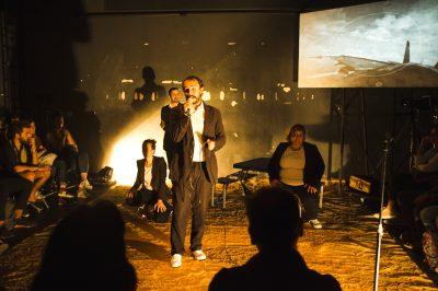 Un groupe de comédiens sur scène, éclairés par un projecteur au fond. Un écran montre un paysage gris.