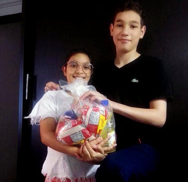 La photo montre deux enfants les bras chargés de denrées alimentaires à Florencia.