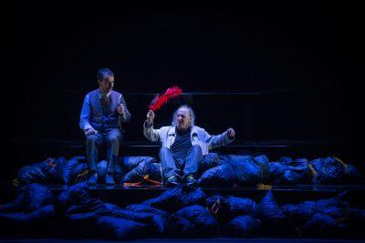Deux hommes assis, entourés de corps inertes. L'un d'eux, plus bas que l'autre, agite une plume rouge.