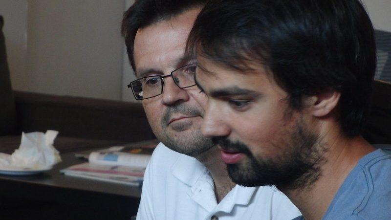 Gros plans sur les visages de Chris Chalcraft et Greg Partyka concentrés pendant un hackathon de géophysique.