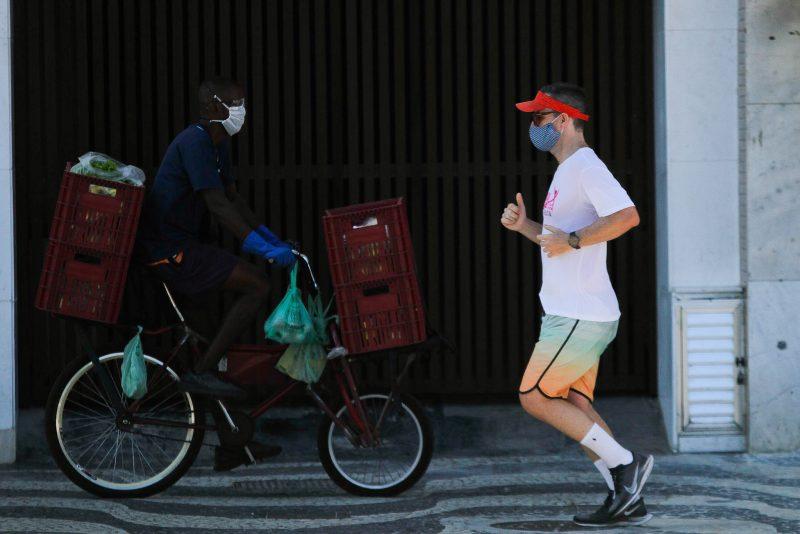 Un homme fait son jogging et un livreur se déplace à vélo. Tous deux portent un masque facial.
