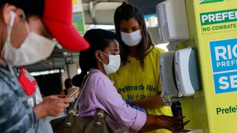 Une femme portant un masque se lave les mains à une station de lavage à Rio, sous les yeux d'un agent de la municipalité.