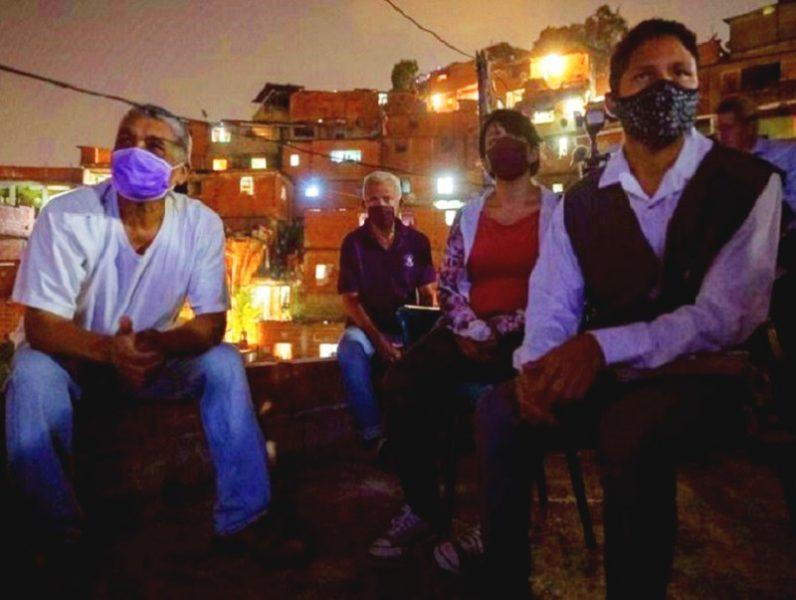 Des habitants du quartier de Petare sont installés sur un toit pour assister à la projection d'un film organisée par Zona de Descarga.