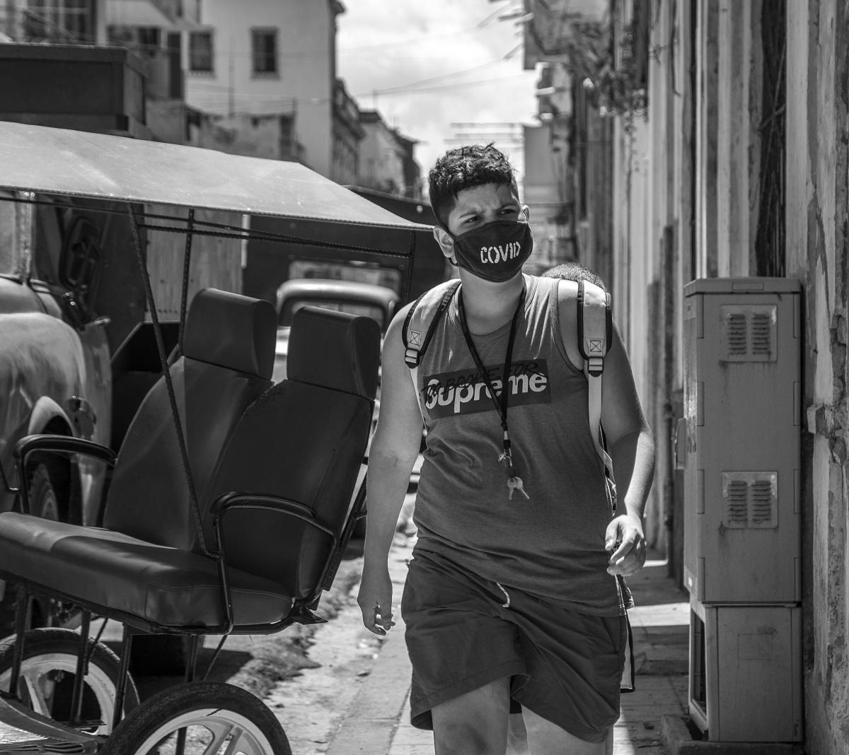 Photo noir et blanc. Un adolescent marche sur un trottoir, il porte un masque portant l'inscription COVID. Un bicytaxi est stationné dans la rue.