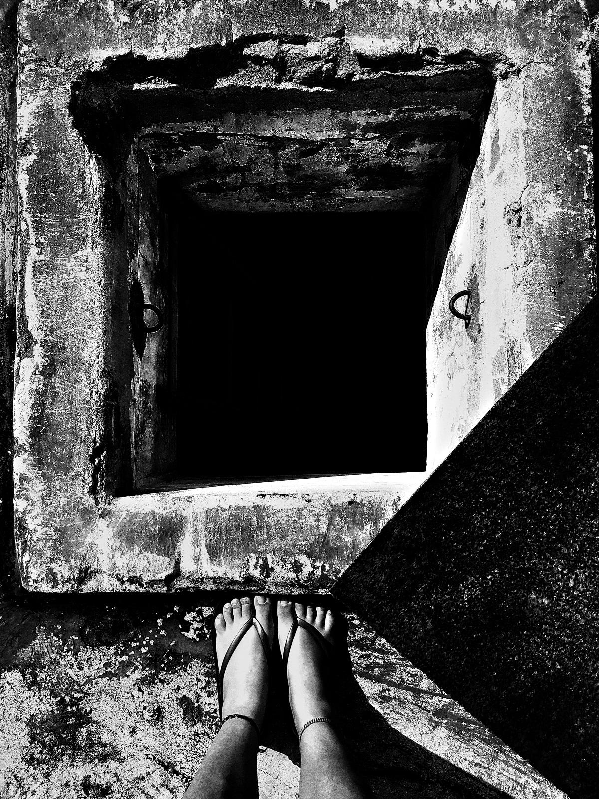 Photo noir et blanc. Une personne dont on ne voit que les chevilles et les deux pieds chaussés de tongs se trouve devant un puits carré dont le fond n'est pas visible.