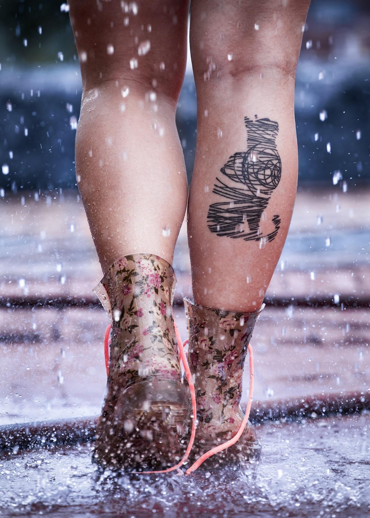 Photo couleur montrant une paire de jambes vue de derrière. La personne porte des bottines transparentes fleuries dont les lacets sont défaits et un chat est tatoué sur l'arrière de son mollet droit. Elle marche dans une flaque d'eau et des gouttes d'eau jaillissent autour d'elle.