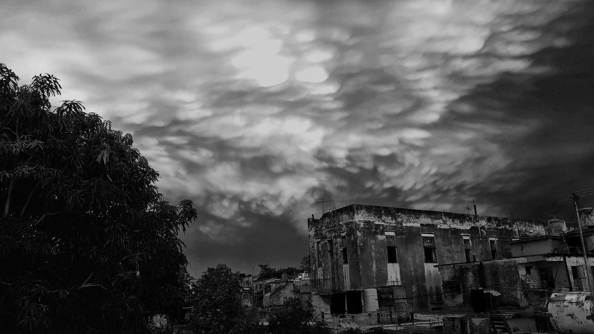 Photo noir et blanc. Sur la droite, un bâtiment vétuste et probablement désaffecté se découpe sur un ciel de fin du jour chargé de nuages bas. Sur la gauche, un ou plusieurs arbres forment une masse arrondie et sombre.