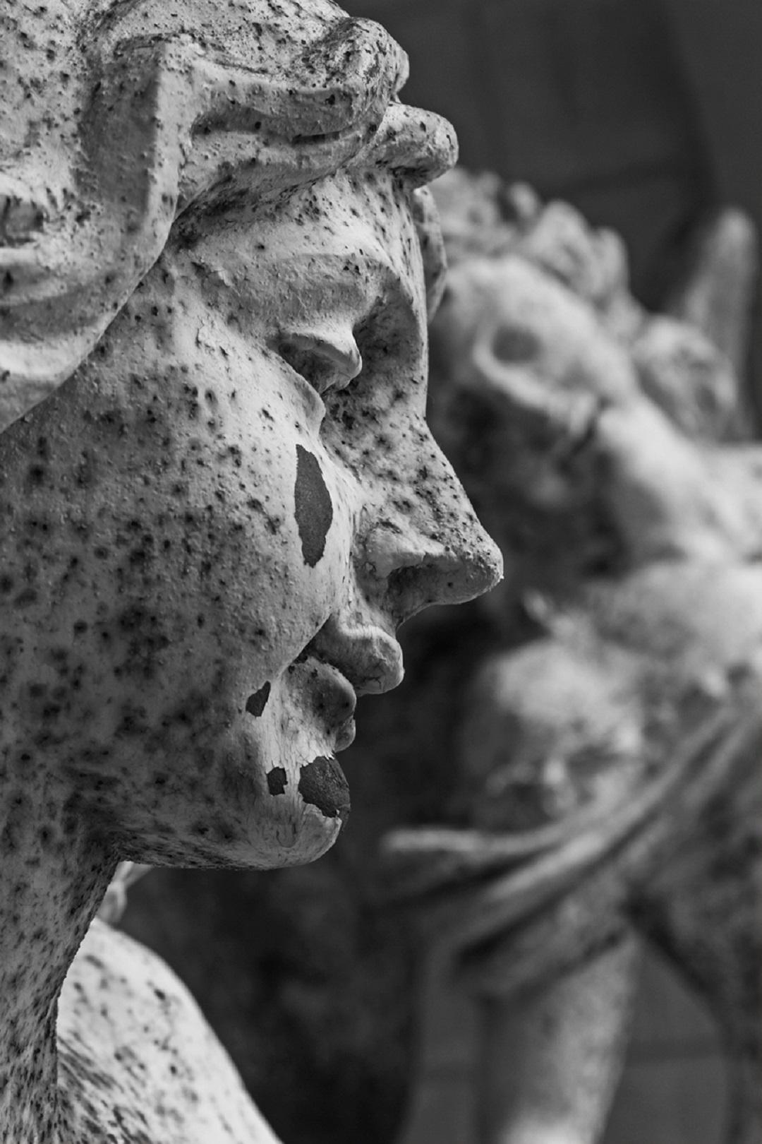 Photo noir et blanc. Le visage d'une statue féminine apparait en gros plan ; une tache sur sa joue laisse à penser qu'elle pleure.