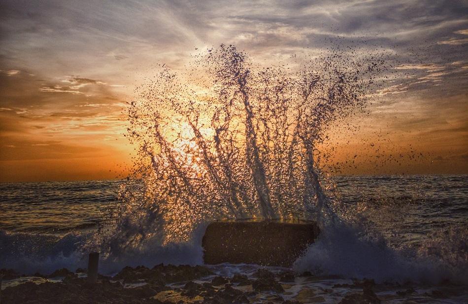 Photo couleur représentant un coucher de soleil sur la mer. Au premier plan se devinent les cailloux ou rochers du rivage et une immense gerbe d'eau s'élève au contact d'un bloc qui se trouve dans l'eau. Le ciel est magnifique, orange et argenté.