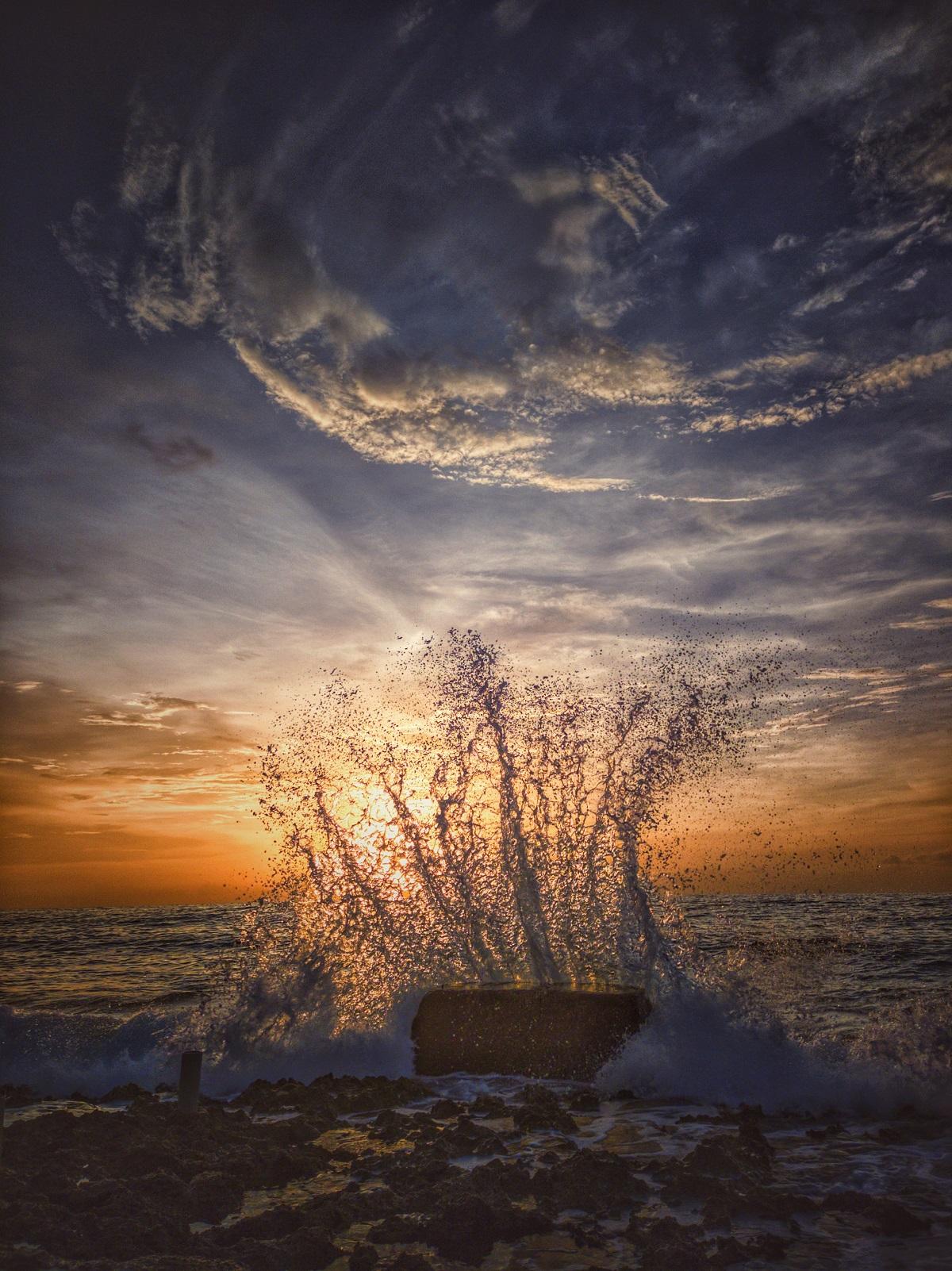Photo couleur représentant un coucher de soleil sur la mer. Au premier plan se devinent les cailloux ou rochers du rivage et une immense gerbe d'eau s'élève au contact d'un bloc (bois, rocher?) qui se trouve dans l'eau. Le ciel est magnifique, orange et argenté.