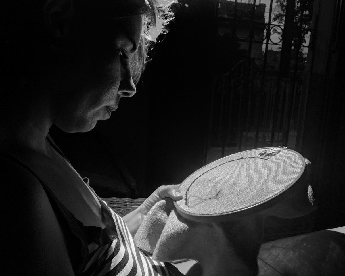 Photo noir et blanc. Une jeune femme est penchée sur une toile à broder et manie l'aiguille.